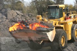 Photo of a bucket loader carrying hot Slag