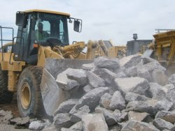 Photo of a payloader working with chunks of recycled concrete and asphalt