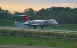 Photo of a small passenger jet landing on a concrete runway