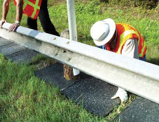 Photo of workers installing recycled rubber anti-vegetation material under a highway guard rail