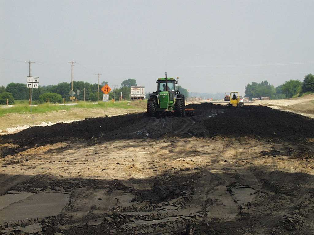 Photo of equipment placing foundry sand for a roadway base